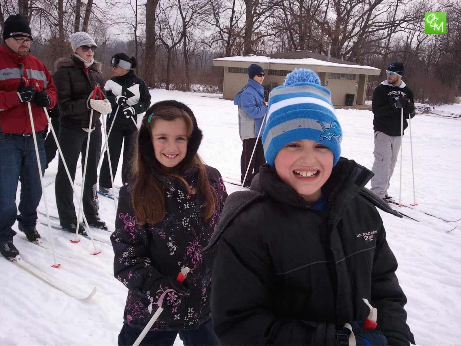 Two young children and family getting ready to cross country ski at one of the Oakland County parks.